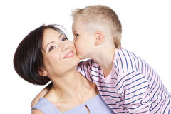 Little boy kissing beautiful mother over white. Little son kissing his happy smiling mother on a cheek over white Stock Photography