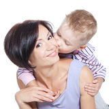 Little boy kissing beautiful mother over white. Little son kissing his happy smiling mother on a cheek over white Stock Images