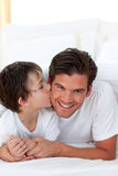 Little boy kissing his father lying on bed. Happy Little boy kissing his father lying on bed Royalty Free Stock Photos