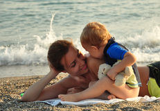 Little boy kissing his mother. On the beach Stock Photos
