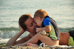 Little boy kissing his mother. On the beach Royalty Free Stock Photography
