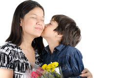 Little boy kissing his mother with flower. On white background Royalty Free Stock Photo