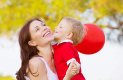 Little boy kissing mom. Image of cute little boy kissing mom, beautiful brunette women with adorable child having fun outdoor in spring time, small kid with red Royalty Free Stock Photos