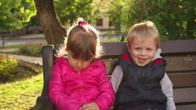 Little boy kissing sad little girl on a Park bench. Fun boy three or four years kissing sad girl outdoors during a walk in the Park. Cute little kids in the Park stock footage