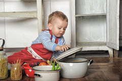 Little boy in the kitchen. Kalenky boy aprons in the kitchen of dishes and products royalty free stock image