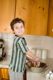 Little boy in the kitchen baking. Six year old boy in the kitchen stirring a bowl while baking Stock Image