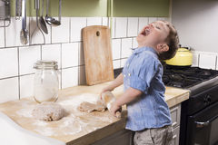 Little boy in the kitchen. Two year old boy rolling dough in the kitchen and acting silly Royalty Free Stock Photography