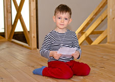 Little boy kneeling on the floor reading Royalty Free Stock Photo