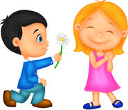 Little boy kneels on one knee giving flowers to girl Stock Image