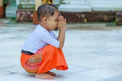 LITTLE BOY KNEELS AND PRAYS AT SHWEDAGON TEMPLE.. Stock Image