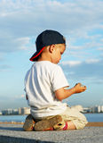 Little boy kneels on the quay Stock Images