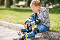 Little boy lace his roller skate sitting on the sidewalk Stock Image