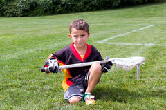 Little boy lacrosse player in the park kneeling down and posing Royalty Free Stock Photo