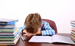 Little boy laid his head on the desk. On the light background, horizontal Royalty Free Stock Photos