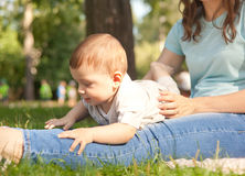 Little boy on the lap of his mother in a summer park. Family, lo Stock Photo