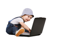 Little boy with a laptop. Little boy sitting with a laptop isolated on the white royalty free stock photos