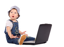 Little boy with a laptop. Little boy sitting with a laptop isolated on the white stock images