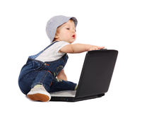 Little boy with a laptop. Little boy sitting with a laptop isolated on the white stock photo