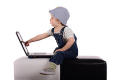 Little boy with a laptop. Little boy sitting with a laptop isolated on the white royalty free stock photography