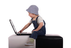 Little boy with a laptop. Little boy sitting with a laptop isolated on the white Royalty Free Stock Images