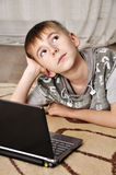 Little boy with laptop. Happy little boy with laptop lying on the floor at home - indoors Royalty Free Stock Photography