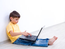 Little boy with laptop in empty room Stock Photos