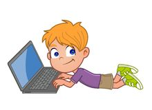 Little boy on laptop. Kid lying on the floor using laptop computer Royalty Free Stock Image
