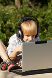 Little boy with laptop in park Royalty Free Stock Photography