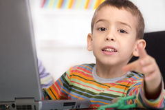 Little boy with laptop shows Stock Photo