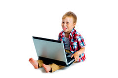 Little boy with a laptop sitting on the floor Stock Images