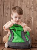 Little boy with large school bag on wooden background.  royalty free stock photo
