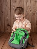 Little boy with large school bag on wooden background.  royalty free stock images