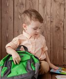 Little boy with large school bag on wooden background.  royalty free stock photos