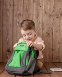 Little boy with large school bag on wooden background.  stock image