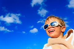 Little boy laugh wrapped in beach towel on sky Stock Photo