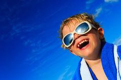Little boy laugh wrapped in beach towel on sky Royalty Free Stock Photos