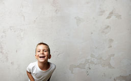 Little boy laughing at the camera. Cocrete wall on Royalty Free Stock Image