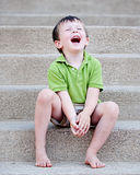 Little Boy Laughing on Steps Stock Image