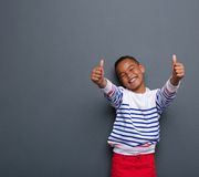 Little boy laughing with thumbs up sign Stock Images