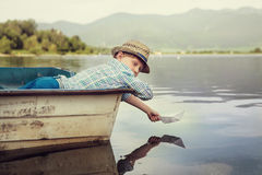 Little boy launch paper ship lying in old boat Royalty Free Stock Image