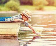 Little boy launch paper ship from old boat on the lake Royalty Free Stock Image