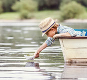 Little boy launch paper ship from old boat on the lake Stock Images
