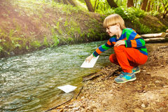 Little boy launching paper ships from riverside Royalty Free Stock Image