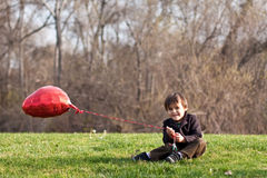 Little boy on lawn with red heart balloon Stock Photos