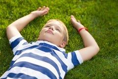 Little boy lay down on the grass Stock Photos
