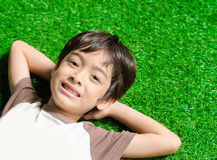 Little boy lay down on green grass Royalty Free Stock Image