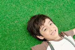 Little boy lay down on green grass Stock Image