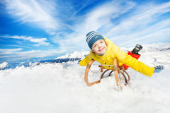 Little boy lay on sledge smile and slide down. Little boy in yellow coat on sledge and stretched hands in the mountain Royalty Free Stock Photography