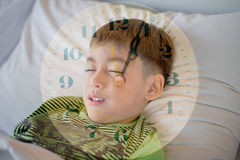 Little boy laying down on the bed with clock exporsure Royalty Free Stock Photo