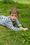 Little boy laying in green grass. Six year old boy laying in green grass outdoors in the summertime Royalty Free Stock Photo